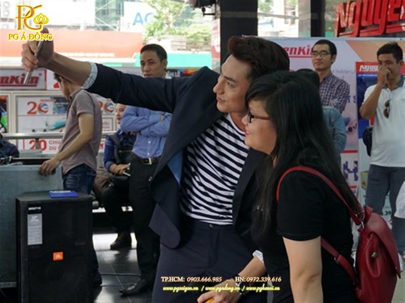 Nam ca sĩ Isaac - đại sứ thương hiệu cho dòng sản phẩm Galaxy J - chụp selfie cùng một khách hàng bằng Galaxy J7 Prime tại siêu thị điện máy Nguyễn Kim vào sáng 23/9
